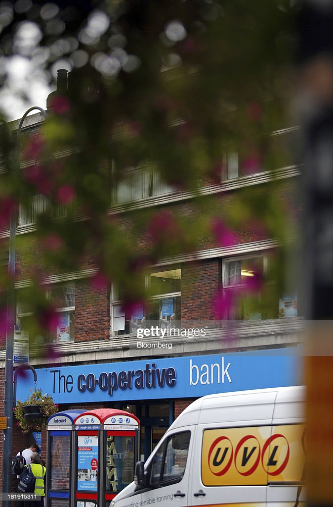 A logo sits on a sign above the entrance to a Co-Operative Bank Plc branch, a unit of Co-Operative Group Ltd., in Leeds, U.K., on Wednesday, Sept. 25, 2013. The parent of Co-operative Bank, which is seeking capital after losses, may avoid being forced to rescue the lender thanks to an accord it struck with regulators last year, according to bondholders. Photographer: Paul Thomas/Bloomberg via Getty Images