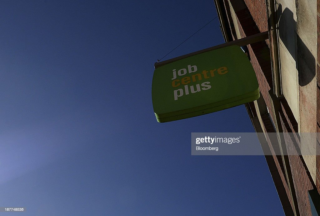 A logo sits on a sign as it stands outside a job centre in Leeds, U.K., on Tuesday, Nov. 12, 2013. Under Bank of England Governor Mark Carney's forward-guidance policy, the central bank has pledged to not to withdraw stimulus at least until unemployment falls to 7 percent. Photographer: Nigel Roddis/Bloomberg via Getty Images
