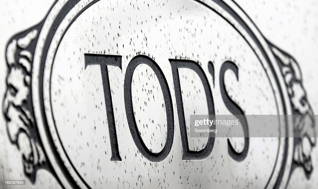 A logo sits on a sign at the entrance to the headquarters of Tod's SpA in Sant'Elpidio a Mare, near Civitanova Marche, Italy, on Wednesday, March 6, 2013. Tod's, the maker of luxury footware and clothing accessories, is due to report earnings for 2012 on March 13. Photographer: Alessia Pierdomenico/Bloomberg via Getty Images