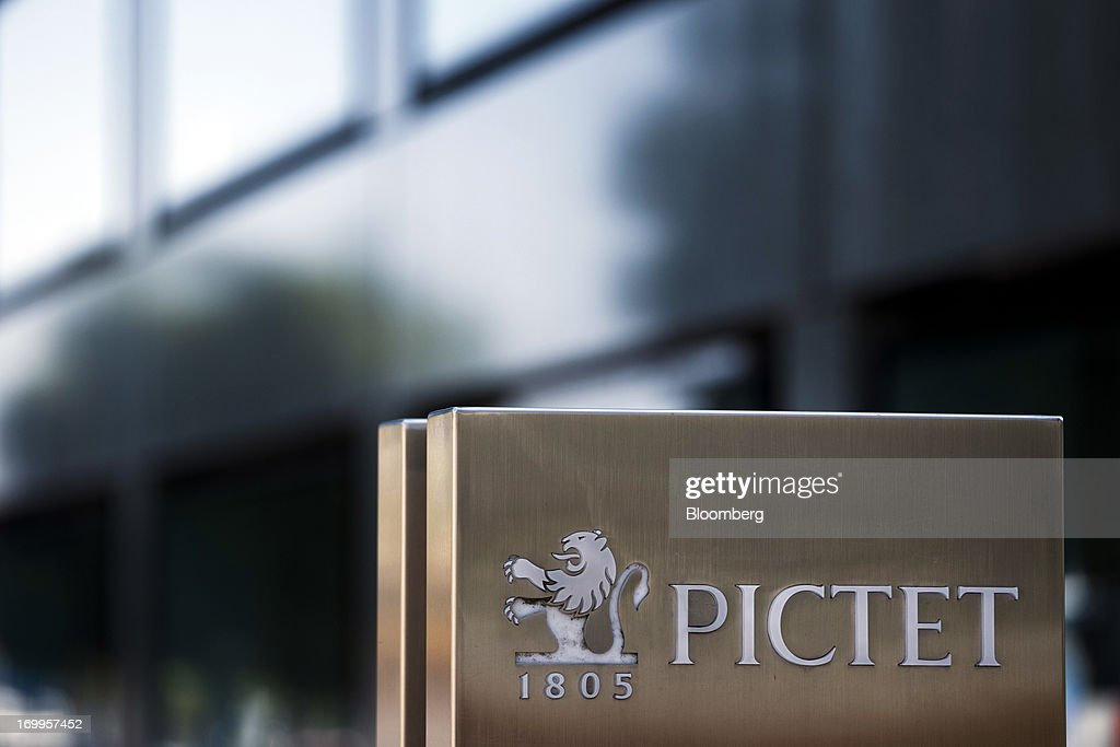 A logo sits on a sign in front of the Pictet & Cie headquarters in Geneva, in Geneva, Switzerland, on Wednesday, June 5, 2013. Members of the Swiss parliament's upper house's economic committee have been debating a law which, if passed, could authorize Swiss banks to cooperate with U.S. authorities. Photographer: Valentin Flauraud/Bloomberg via Getty Images