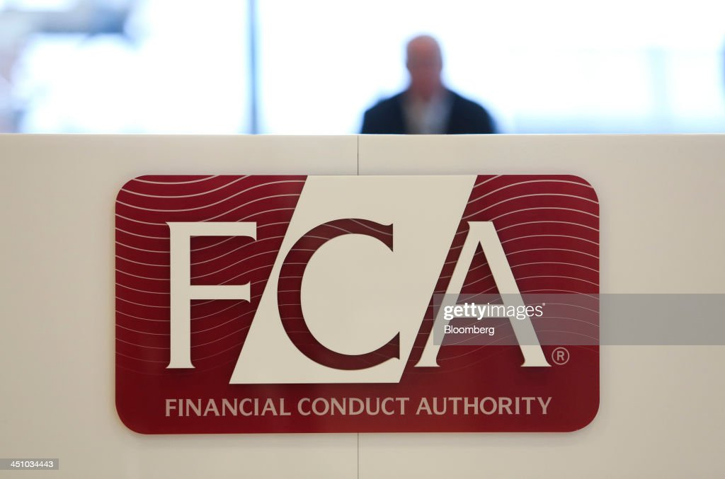 A logo sits on a sign in the reception area of the headquarters of the Financial Conduct Authority (FCA) in the Canary Wharf business district in London, U.K., on Thursday, Nov. 21, 2013. The FCA is working with regulators including the U.S. Department of Justice and the Commodity Futures Trading Commission to investigate the potential manipulation of the foreign-exchange market. Photographer: Chris Ratcliffe/Bloomberg via Getty Images