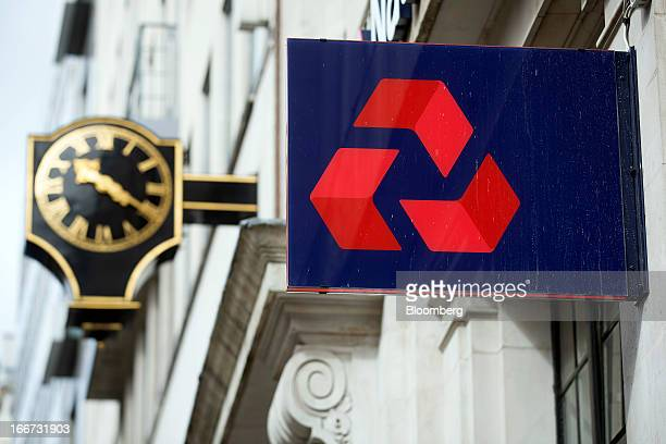 A logo sits on a sign outside a branch of NatWest bank part of the Royal Bank of Scotland Group Plc in London UK on Tuesday April 16 2013 The UK's...