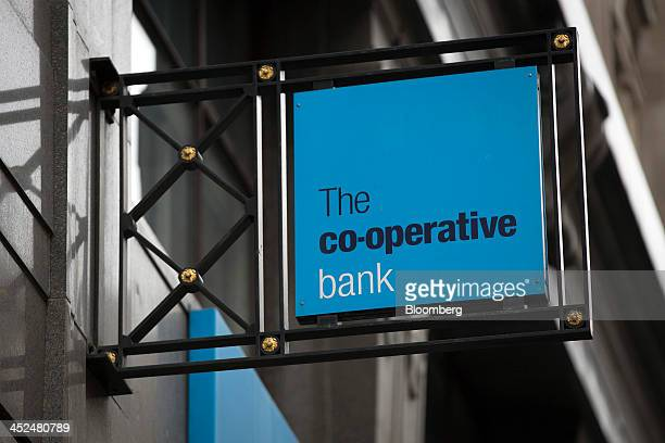 A logo sits on a sign outside a CoOperative Bank Plc bank branch in London UK on Friday Nov 29 2013 CoOperative Bank Plc which is trying to plug a 15...