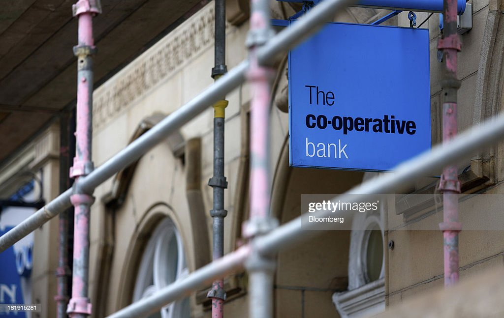A logo sits on a sign outside a Co-Operative Bank Plc branch, a unit of Co-Operative Group Ltd., in Huddersfield, U.K., on Wednesday, Sept. 25, 2013. The parent of Co-operative Bank, which is seeking capital after losses, may avoid being forced to rescue the lender thanks to an accord it struck with regulators last year, according to bondholders. Photographer: Paul Thomas/Bloomberg via Getty Images