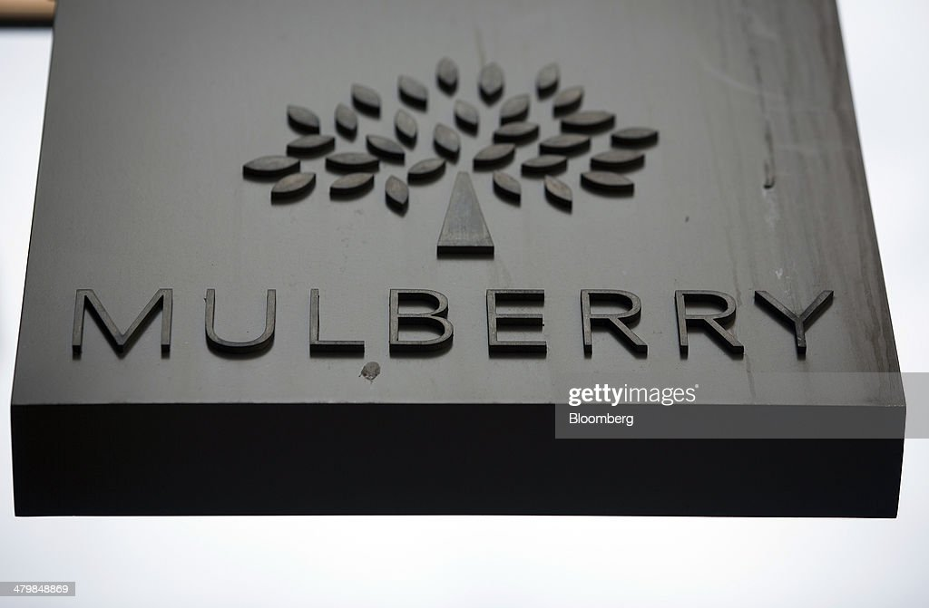 A logo sits on a sign outside a Mulberry Group Plc luxury store on New Bond Street in London, U.K., on Thursday, March 20, 2014. Mulberry Group said Bruno Guillon will step down as chief executive officer after two years during which the British luxury handbag maker lost two-thirds of its market value. Photographer: Simon Dawson/Bloomberg via Getty Images
