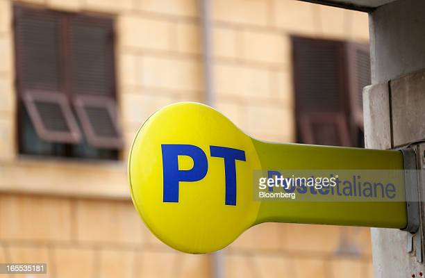 A logo sits on a sign outside a Poste Italiane SpA post office in Rome Italy on Thursday April 4 2013 Italy's stateowned postal service and Wind SpA...