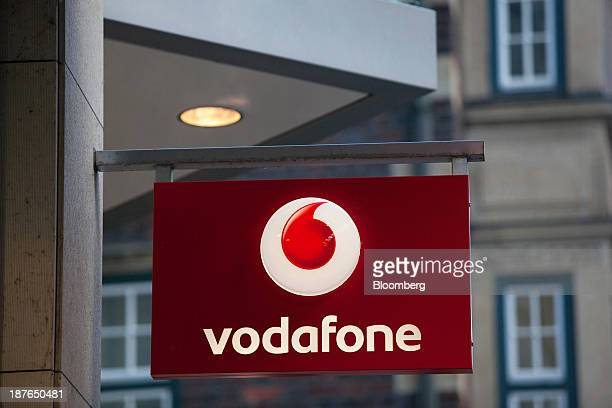 A logo sits on a sign outside a Vodafone store operated by Vodafone Group Plc in Hamburg Germany on Saturday Nov 9 2013 While Germany's economic...