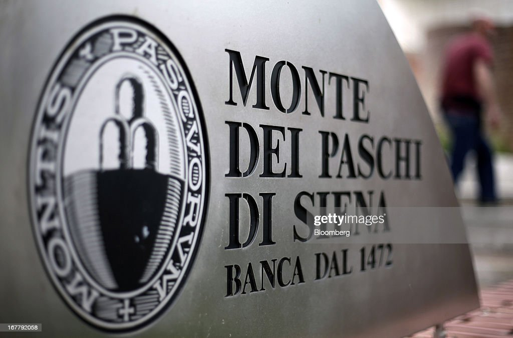 A logo sits on a sign outside Banca Monte dei Paschi di Siena SpA's administrative offices in Siena, Italy, on Monday, April 29, 2013. An Italian judge rejected a request by prosecutors to seize as much as 1.95 billion euros ($2.5 billion) of assets held by Nomura Holdings Inc. as they probed how Banca Monte dei Paschi di Siena SpA used derivatives to conceal losses. Photographer: Alessia Pierdomenico/Bloomberg via Getty Images