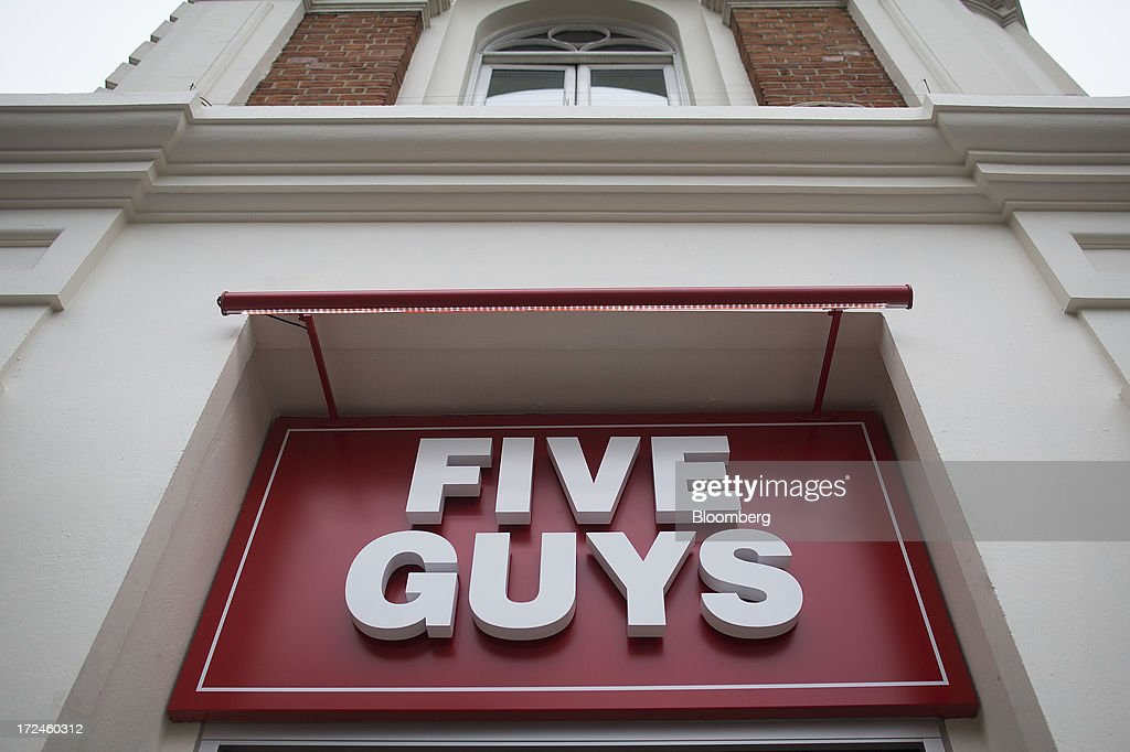 A logo sits on a sign outside the first U.K. outlet of U.S. burger restaurant chain Five Guys in London, U.K., on Tuesday, July 2, 2013. Five Guys, which is set to open its first U.K. store in Covent Garden on July 4, is a family outfit that started in Washington, D.C., in 1986, and has expanded to more than 1,000 locations in the U.S. and Canada. Photographer: Simon Dawson/Bloomberg via Getty Images