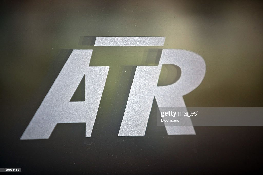 A logo sits on a window at Avions de Transport Regional's (ATR) turboprop aircraft production facility in Colomiers, France, on Wednesday, Jan. 23, 2013. ATR, the world's largest maker of turbo-propeller airliners, reported record profit for 2012, even as it fell short of its shipment target amid production delays. Photographer: Balint Porneczi/Bloomberg via Getty Images