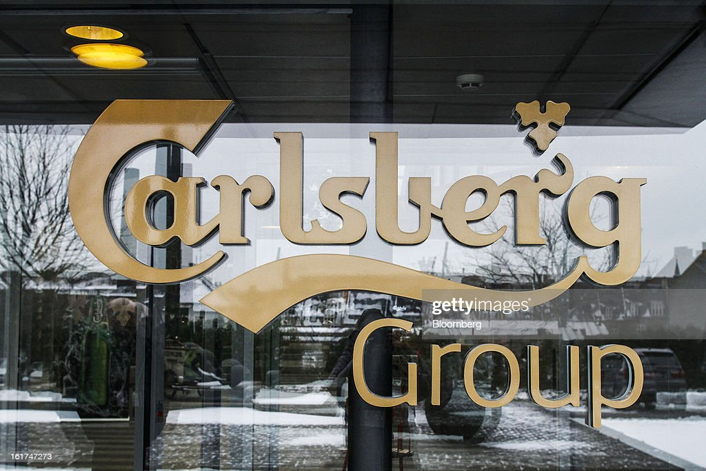 A logo sits on a window at the entrance to the headquarters of Carlsberg A/S in Copenhagen, Denmark, on Thursday, Feb. 14, 2013. Danish brewer Carlsberg A/S owns France's biggest beer brand Kronenbourg. Photographer: Freya Ingrid Morales/Bloomberg via Getty Images