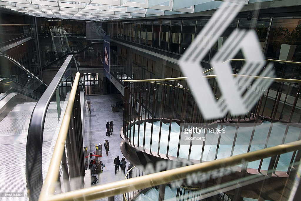 A WSE logo sits on display above visitors in the main hall at the Warsaw Stock Exchange in Warsaw, Poland, on Thursday, April 11, 2013. Poland's central bank kept interest rates unchanged at a record-low 3.25 percent yesterday. Photographer: Bartek Sadowski/Bloomerg