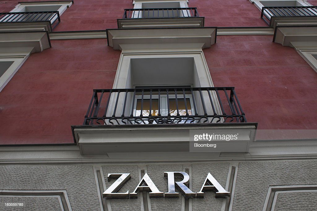 A logo sits on display beneath balconies above a Zara fashion store, operated by Inditex SA, in Madrid, Spain, on Tuesday, March 12, 2013. Europe's richest man, Amancio Ortega, the 76-year-old founder of Inditex SA, the world's biggest clothing retailer and owner of the Zara clothing chain, is No. 3 on Standard & Poor's 500 Index with a net worth of $57.4 billion, $4.9 billion ahead of Warren Buffett, 82. Photographer: Angel Navarrete/Bloomberg via Getty Images