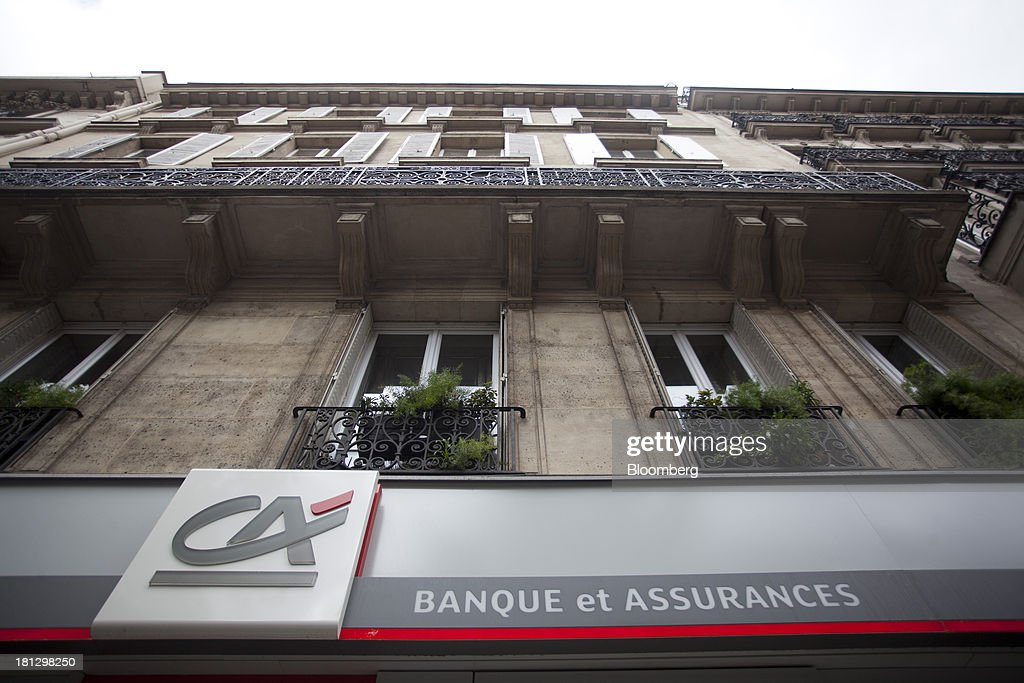 A logo sits on display beneath residential housing outside a Credit Agricole SA bank branch in Paris, France, on Thursday, Sept. 19, 2013. Bank of France General Council member Bernard Maris said France will end up restructuring its debt as tax 'optimization' by large companies including Google Inc. will leave too big a burden on the middle class. Photographer: Balint Porneczi/Bloomberg via Getty Images
