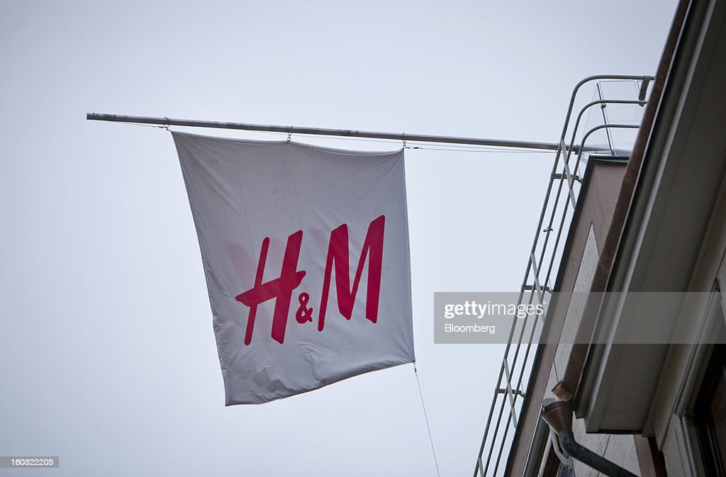 A logo sits on display on a banner hanging from the roof of a Hennes & Mauritz AB (H&M) store in Stockholm, Sweden, on Tuesday, Jan. 29, 2013. Hennes & Mauritz AB, Europe's second-largest clothing retailer, reported sales growth that beat analysts' estimates for a second consecutive month as the chain offered markdowns in advance of the Christmas holiday. Photographer: Casper Hedberg/Bloomberg via Getty Images