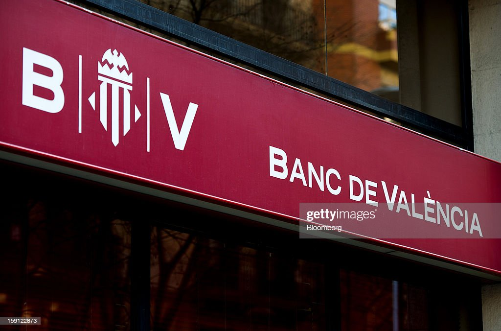 A logo sits on display outside a Banco de Valencia SA bank branch in Barcelona, Spain, on Tuesday, Jan. 8, 2013. Banco Santander SA, Spain's biggest lender, will offer 263 million euros ($345 million) in stock to buy out minority investors in its Banco Espanol de Credito SA retail unit and close 700 local branches to cut costs. Photographer: David Ramos/Bloomberg via Getty Images