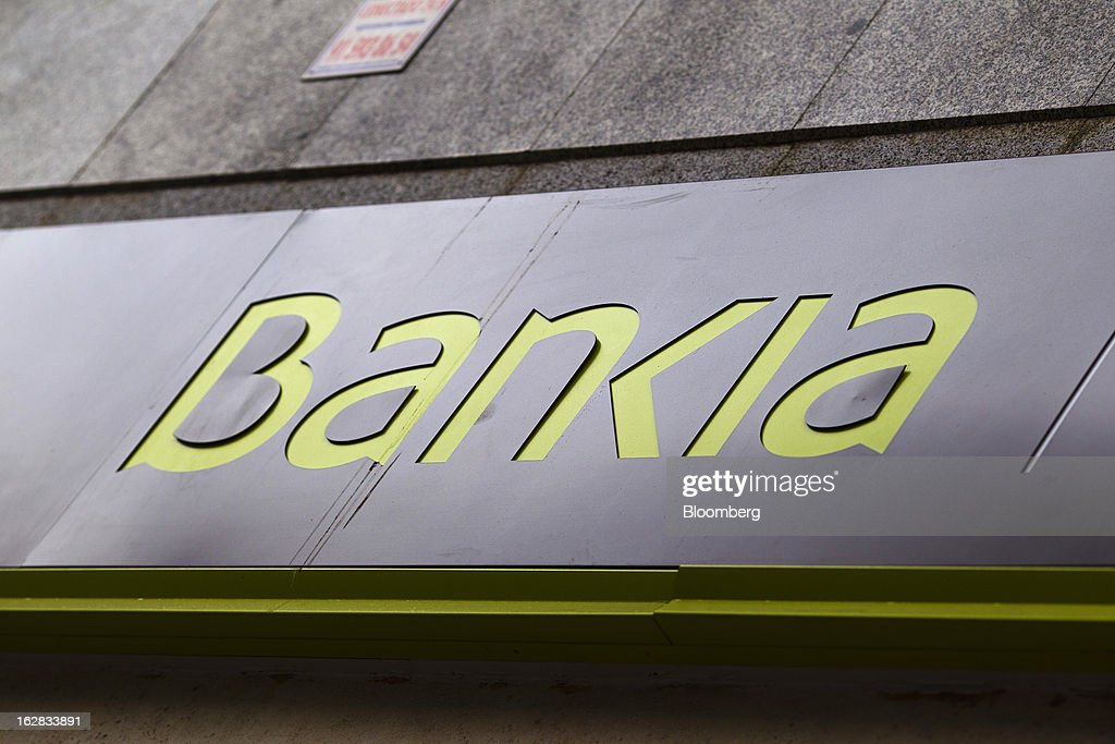 A logo sits on display outside a Bankia SA bank branch in Madrid, Spain, on Thursday, Feb. 28, 2013. BFA-Bankia Chairman Jose Ignacio Goirigolzarri said a balance sheet clean-up that inflicted a 21.2 billion-euro ($27.6 billion) after-tax loss last year will set the Spanish banking group on course to repay state aid. Photographer: Angel Navarrete/Bloomberg via Getty Images