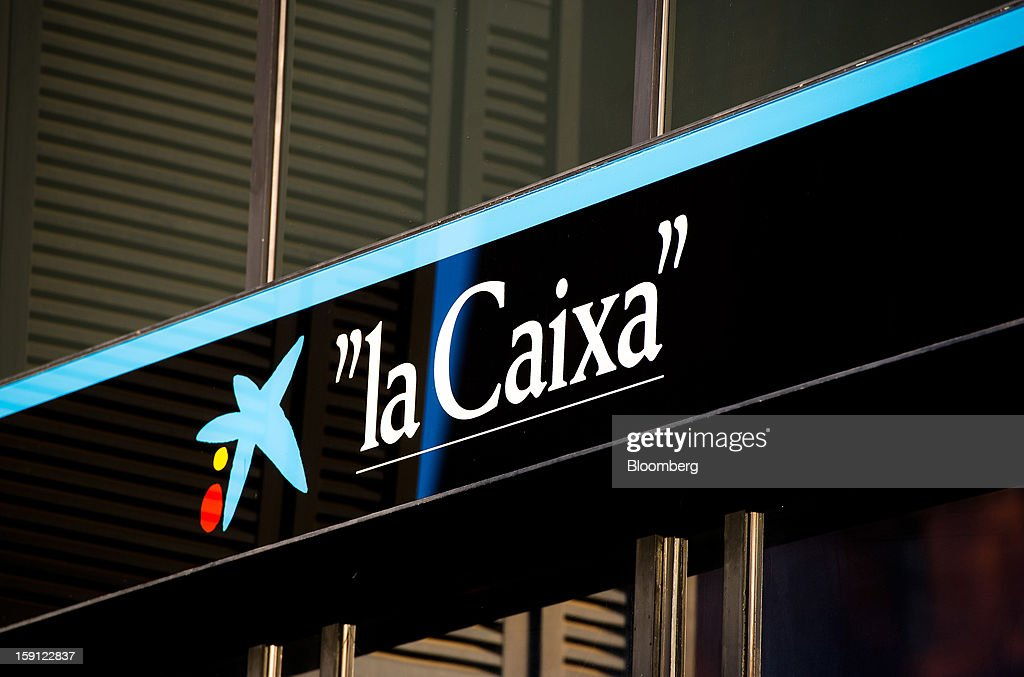 A logo sits on display outside a CaixaBank SA bank branch in Barcelona, Spain, on Tuesday, Jan. 8, 2013. Banco Santander SA, Spain's biggest lender, will offer 263 million euros ($345 million) in stock to buy out minority investors in its Banco Espanol de Credito SA retail unit and close 700 local branches to cut costs. Photographer: David Ramos/Bloomberg via Getty Images
