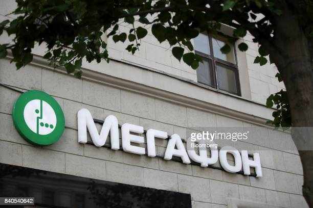 A logo sits on display outside a MegaFon PJSC mobile phone store in Moscow Russia on Tuesday Aug 29 2017 MegaFon considers various alternatives for...