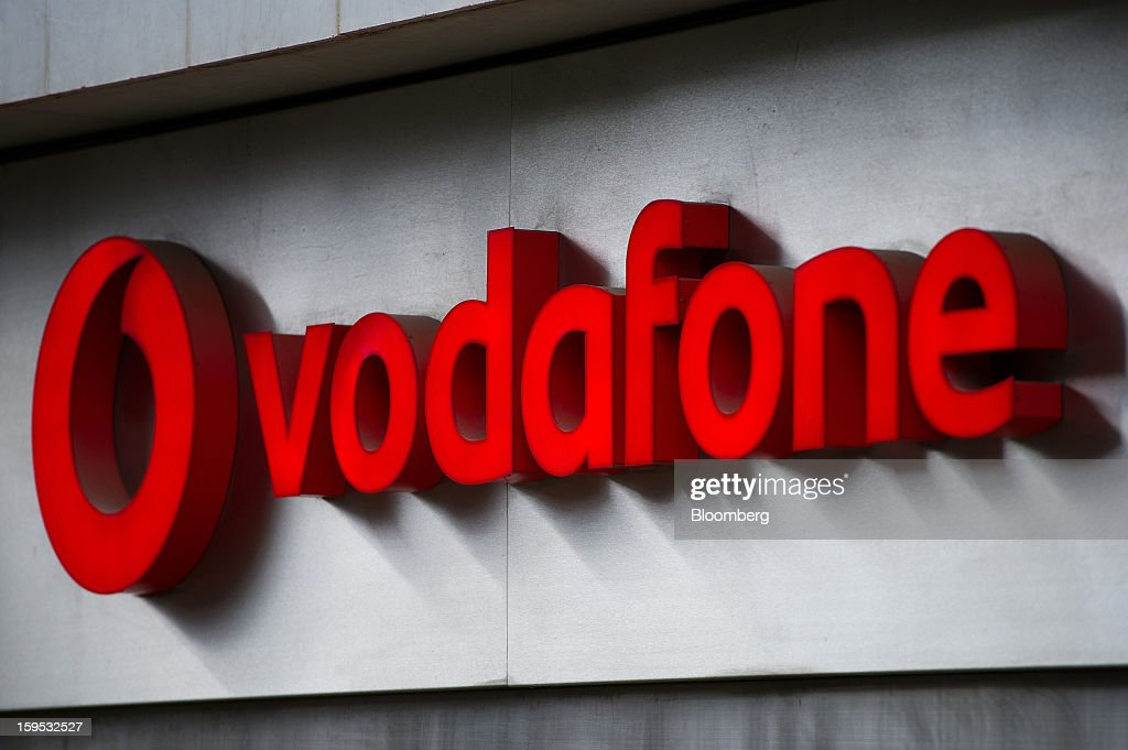 A logo sits on display outside a Vodafone Group Plc store in Barcelona, Spain, on Tuesday, Jan. 15, 2013. Vodafone Group Plc, the world's second largest mobile-phone company, plans to reduce the workforce at its Spanish unit as unemployment exceeding 25 percent in the recession-plagued country causes sales to drop. Photographer: David Ramos/Bloomberg via Getty Images