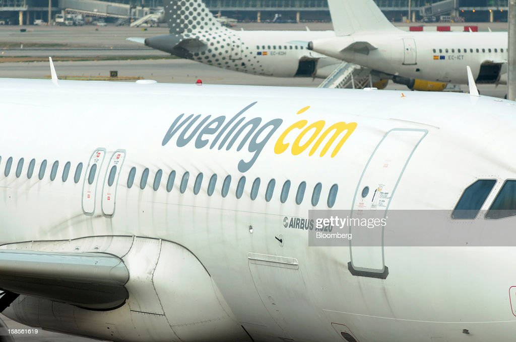 A logo sits on the fuselage of an Airbus A320 aircraft, operated by Vueling Airlines SA, at EL Prat airport in Barcelona, Spain, on Wednesday, Dec. 19, 2012. International Consolidated Airlines Group SA won't require European Union approval to buy 100 percent of low-cost carrier Vueling Airlines SA, the EU's antitrust chief said. Photographer: Stefano Buonamici/Bloomberg via Getty Images