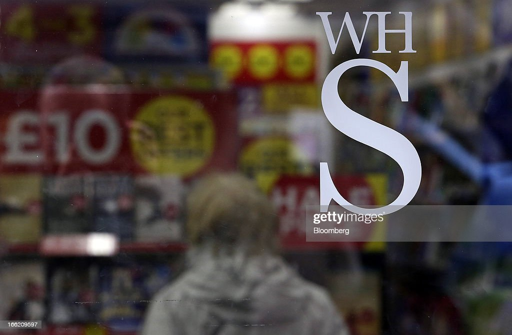 A logo sits on the glass window of a WH Smith Plc store in Folkestone, U.K., on Tuesday, April 9, 2013. WH Smith Plc, the book and magazine retailer with more than 1,100 U.K. outlets, is scheduled to announce earnings on April 11. Photographer: Chris Ratcliffe/Bloomberg via Getty Images