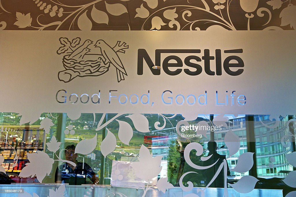 A logo sits on the glass window of the Nestle SA store next to the company's headquarters in Vevey, Switzerland, on Thursday, Oct. 17, 2013. Nestle SA, the world's biggest food company, reported nine-month sales that were below its full-year target rate, highlighting the difficult environment faced by the makers of consumer products. Photographer: Gianluca Colla/Bloomberg via Getty Images