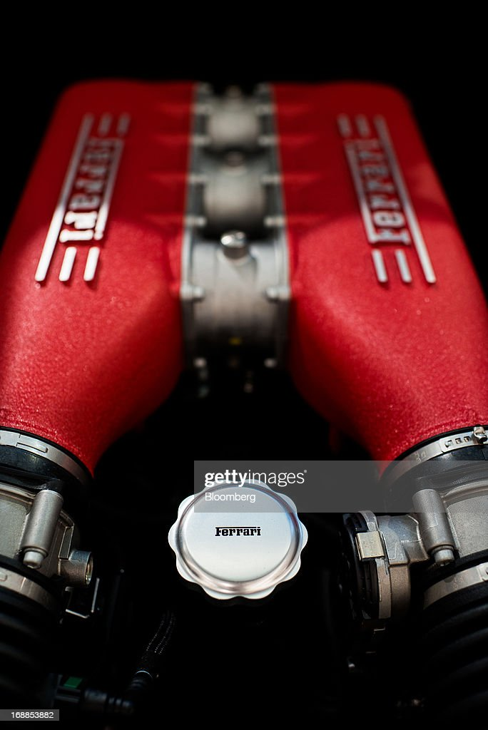 A logo sits on the oil filler cap on the V8 cylinder engine of a Ferrari 458 Italia sports car in the showroom of an automobile dealership in...