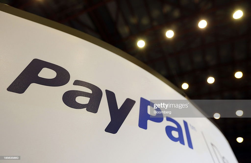 A logo sits on the PayPal company stand, a unit of Ebay Inc., during the Apps World Multi-Platform Developer Show in London, U.K., on Wednesday, Oct. 23, 2013. Retail sales of Internet-connected wearable devices, including watches and eyeglasses, will reach $19 billion by 2018, compared with $1.4 billion this year, Juniper Research said in an Oct. 15 report. Photographer: Chris Ratcliffe/Bloomberg via Getty Images