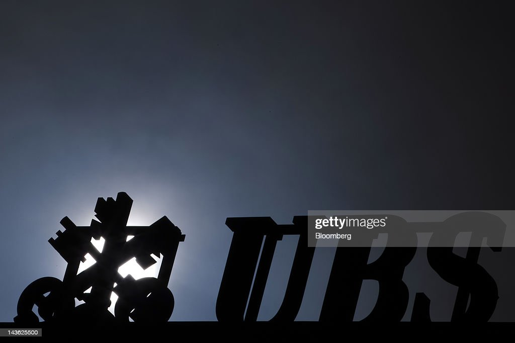 AG logo sits on the roof a bank branch silhouetted by the sun in Geneva, Switzerland, on Tuesday, May 1, 2012. UBS AG will post first quarter earnings earnings on May 2. Photographer: Valentin Flauraud/Bloomberg via Getty Images