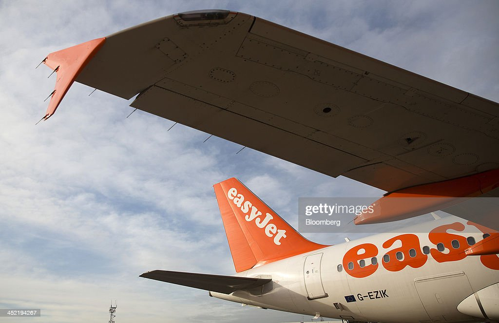 A logo sits on the tailfin of an Airbus A319 aircraft, operated by EasyJet Plc, at the airline's hub at London Luton Airport in Luton, U.K., on Tuesday, Nov. 26, 2013. Shares in International Consolidated Airlines Group SA (IAG) and EasyJet Plc climbed at least 2 percent, pushing a gauge of travel and leisure companies higher, as oil prices slid in reaction to Iran's nuclear deal with world powers. Photographer: Simon Dawson/Bloomberg via Getty Images