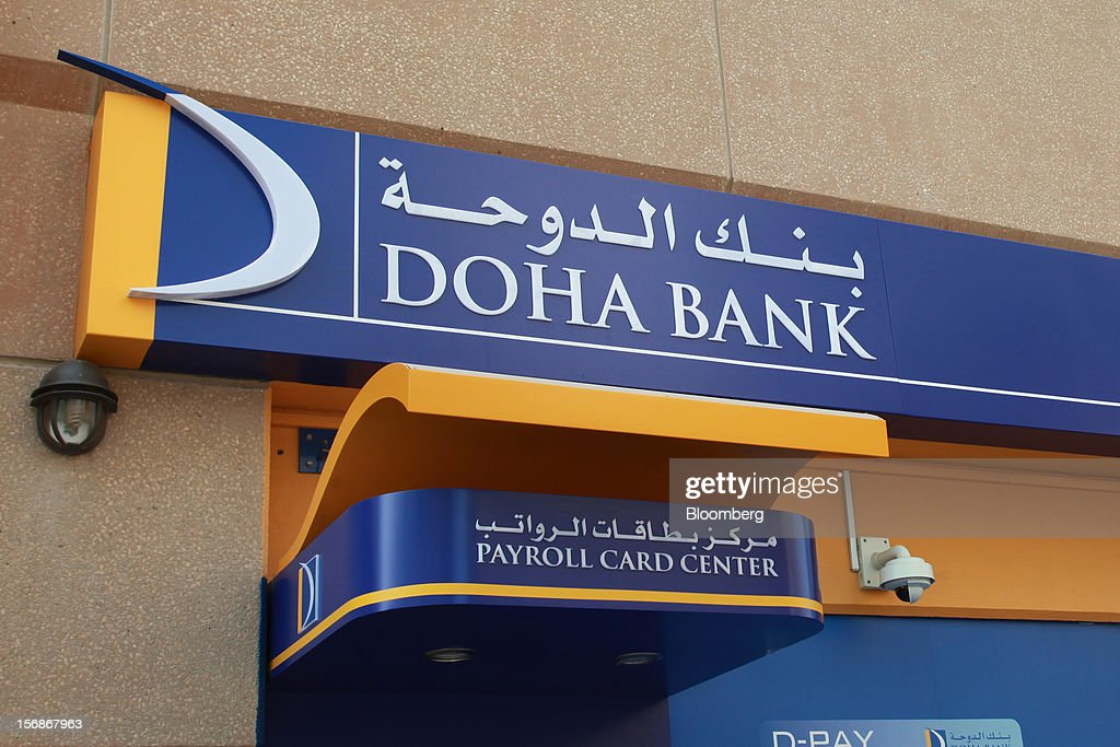 A logo sits outside a payroll card center operated by Doha Bank QSC in Doha, Qatar, on Thursday, Nov. 22, 2012. Qatar Telecom QSC, the country's biggest company by revenue, is seeking a syndicated loan for about $1 billion to refinance existing debt, according to a person with direct knowledge of the deal. Photographer: Gabriela Maj/Bloomberg via Getty Images