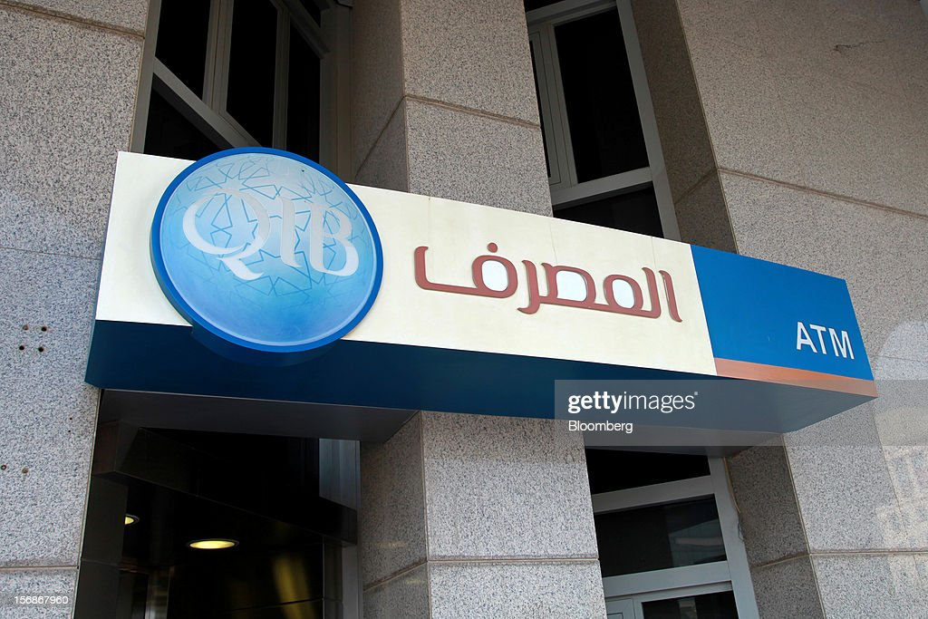 A logo sits outside an automated teller machine (ATM) facility operated by the Qatar Islamic Bank (QIB) in Doha, Qatar, on Thursday, Nov. 22, 2012. Qatar Telecom QSC, the country's biggest company by revenue, is seeking a syndicated loan for about $1 billion to refinance existing debt, according to a person with direct knowledge of the deal. Photographer: Gabriela Maj/Bloomberg via Getty Images