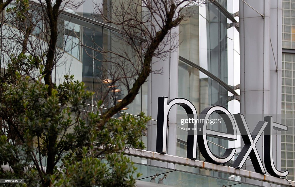 A logo stands above the entrance to a Next Plc store in Manchester, U.K., on Monday, April 1, 2013. U.K. retail sales unexpectedly stagnated in March in a sign that consumer spending remains under pressure from higher energy bills and weak wage growth. Photographer: Paul Thomas/Bloomberg via Getty Images