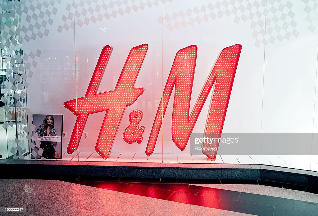 A logo stands illuminated in the window of a Hennes & Mauritz AB (H&M) store in Stockholm, Sweden, on Tuesday, Jan. 29, 2013. Hennes & Mauritz AB, Europe's second-largest clothing retailer, reported sales growth that beat analysts' estimates for a second consecutive month as the chain offered markdowns in advance of the Christmas holiday. Photographer: Casper Hedberg/Bloomberg via Getty Images
