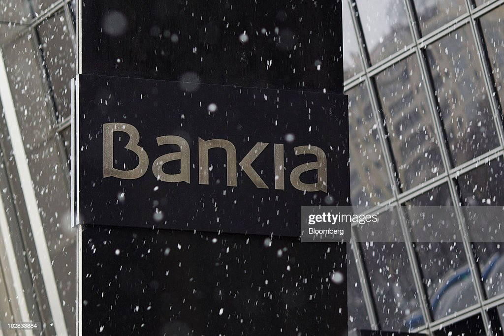 A logo stands on display outside the headquarters of Bankia SA in Madrid, Spain, on Thursday, Feb. 28, 2013. BFA-Bankia Chairman Jose Ignacio Goirigolzarri said a balance sheet clean-up that inflicted a 21.2 billion-euro ($27.6 billion) after-tax loss last year will set the Spanish banking group on course to repay state aid. Photographer: Angel Navarrete/Bloomberg via Getty Images