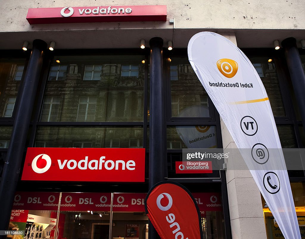 Logos and banners sit on display outside Vodafone Group Plc, left, and Kabel Deutschland Holding AG stores as they sit side by side in Leipzig, Germany, on Wednesday, Sept. 18, 2013. Vodafone Group Plc's 7.7 billion-euro ($10.2 billion) bid for Kabel Deutschland Holding AG cleared a major hurdle by winning the backing of at least 75 percent of the German company's shareholders. Photographer: Krisztian Bocsi/Bloomberg via Getty Images