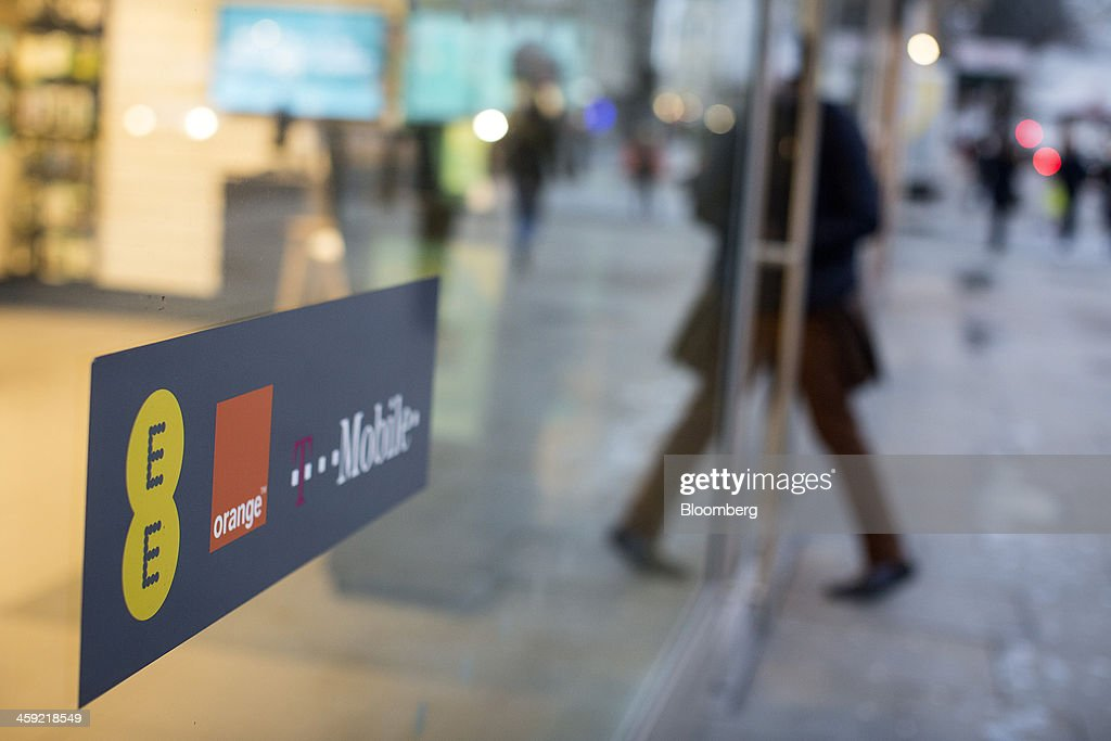 Logos for mobile communications companies EE, Orange SA and T-Mobile, operated by Deutsche Telekom AG, sit on a decal in the window of an EE mobile phone store in London, U.K., on Tuesday, Dec. 24, 2013. Vodafone Group Plc; EE, which is co-owned by Orange SA and Deutsche Telekom AG; Three, owned by Hutchison Whampoa Ltd.; and Virgin Media Inc. said they will cap bills run up on phones reported lost or stolen, stop mid-contract price increases, and support the U.K. government in its attempt to end roaming charges within the European Union. Photographer: Simon Dawson/Bloomberg via Getty Images