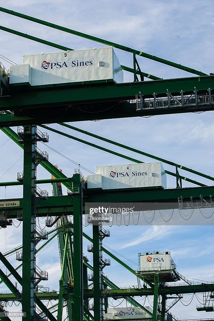Logos for PSA Sines are seen on ship-to-shore cranes on the dockside at the open deep-water Port of Sines in Sines, Portugal, on Tuesday, Dec. 11, 2012. The Portuguese government is ready to implement additional measures in 2013 if there are slippages in meeting budget targets, the European Commission said. Photographer: Mario Proenca/Bloomberg via Getty Images