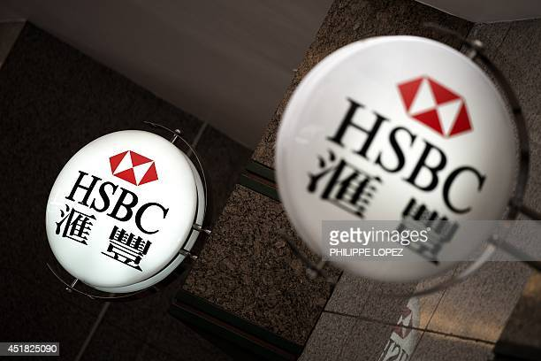 Logos of HSBC are seen on signs outside a branch of the bank in Hong Kong on July 8 2014 Global bank HSBC has downgraded its investment outlook for...