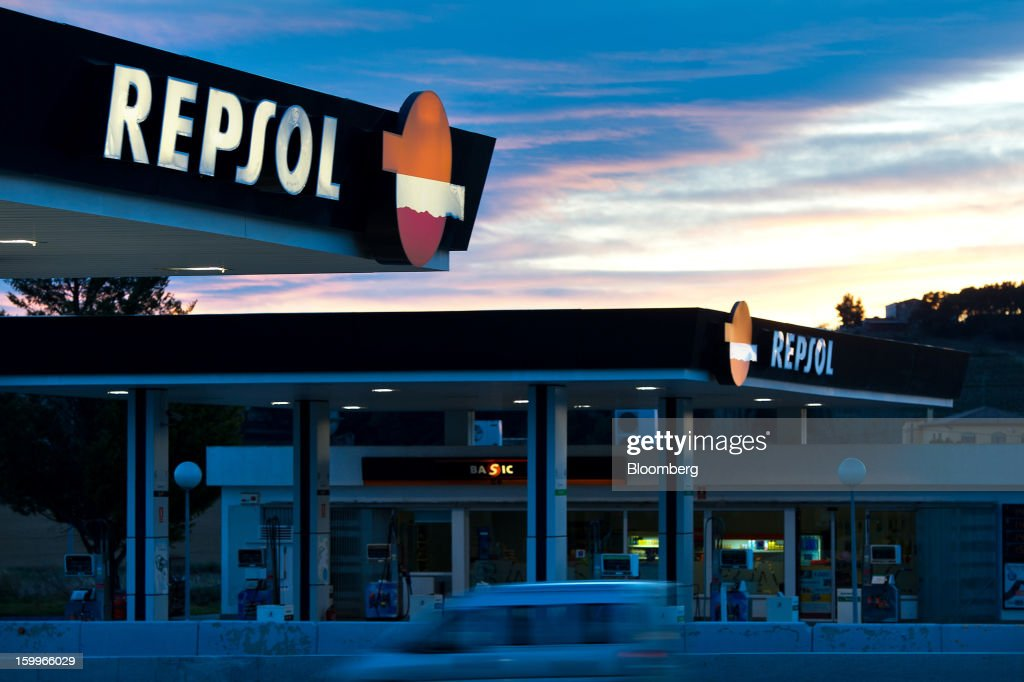 Logos sit illuminated above a Repsol SA gas station at dusk in Puigdalbert, near Barcelona, Spain, on Wednesday, Jan. 23, 2013. Repsol SA, Spain's largest energy company, expects to sell liquefied natural gas assets for about 2 billion euros ($2.7 billion) by early February, according to a person familiar with the matter. Photographer: David Ramos/Bloomberg via Getty Images