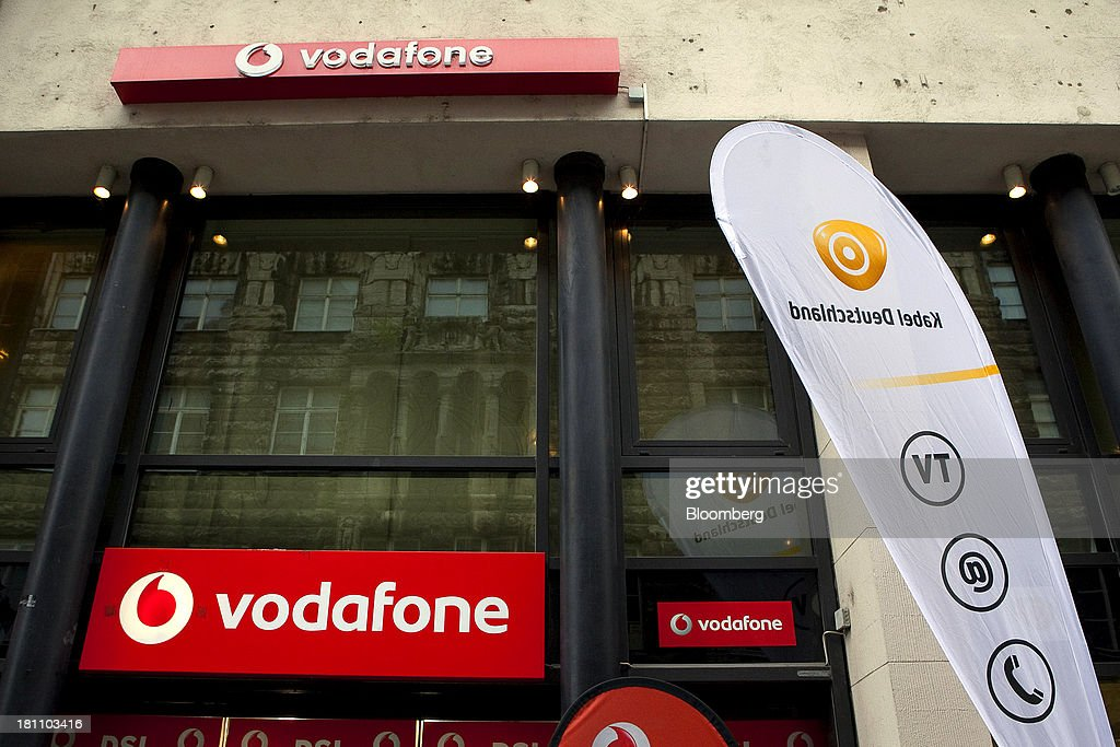 Logos sit on display outside a store operated by Vodafone Group Plc, as a Kabel Deutschland Holding AG banner stands outside their neighboring store in Leipzig, Germany, on Wednesday, Sept. 18, 2013. Vodafone Group Plc's 7.7 billion-euro ($10.2 billion) bid for Kabel Deutschland Holding AG cleared a major hurdle by winning the backing of at least 75 percent of the German company's shareholders. Photographer: Krisztian Bocsi/Bloomberg via Getty Images