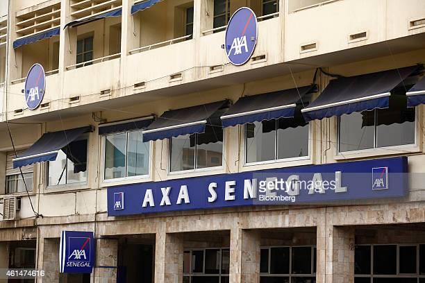 Logos sit on display outside the headquarters of Axa Senegal operated by Axa SA in Dakar Senegal on Monday Jan 12 2015 Dakar with 3 million residents...
