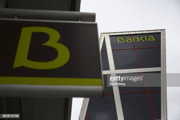 Logos sit on display outside the headquarters of Bankia SA at the Kio towers in Madrid on Wednesday June 28 2017 Bankia SA agreed to acquire Banco...