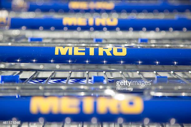 Logos sit on shopping cart handles inside a wholesale store operated by Metro AG in Cologne Germany on Wednesday Jan 7 2014 As European Central Bank...
