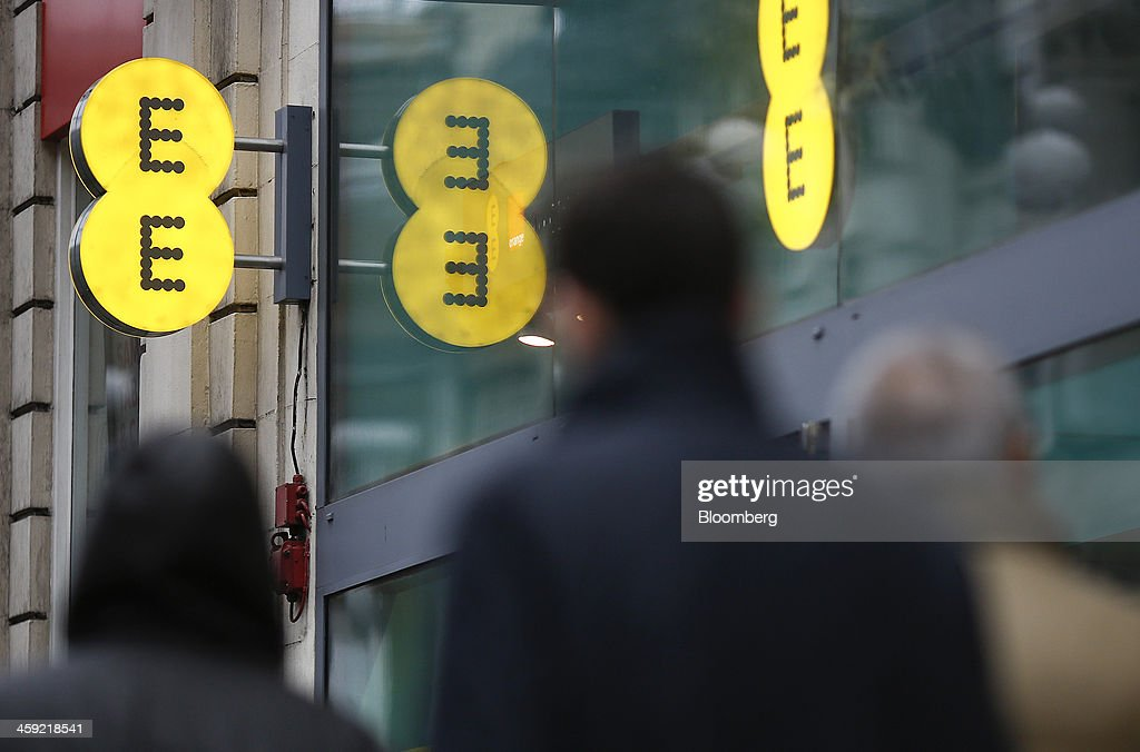Logos sit on signs as pedestrians pass an EE mobile phone store in London, U.K., on Tuesday, Dec. 24, 2013. Vodafone Group Plc; EE, which is co-owned by Orange SA and Deutsche Telekom AG; Three, owned by Hutchison Whampoa Ltd.; and Virgin Media Inc. said they will cap bills run up on phones reported lost or stolen, stop mid-contract price increases, and support the U.K. government in its attempt to end roaming charges within the European Union. Photographer: Simon Dawson/Bloomberg via Getty Images