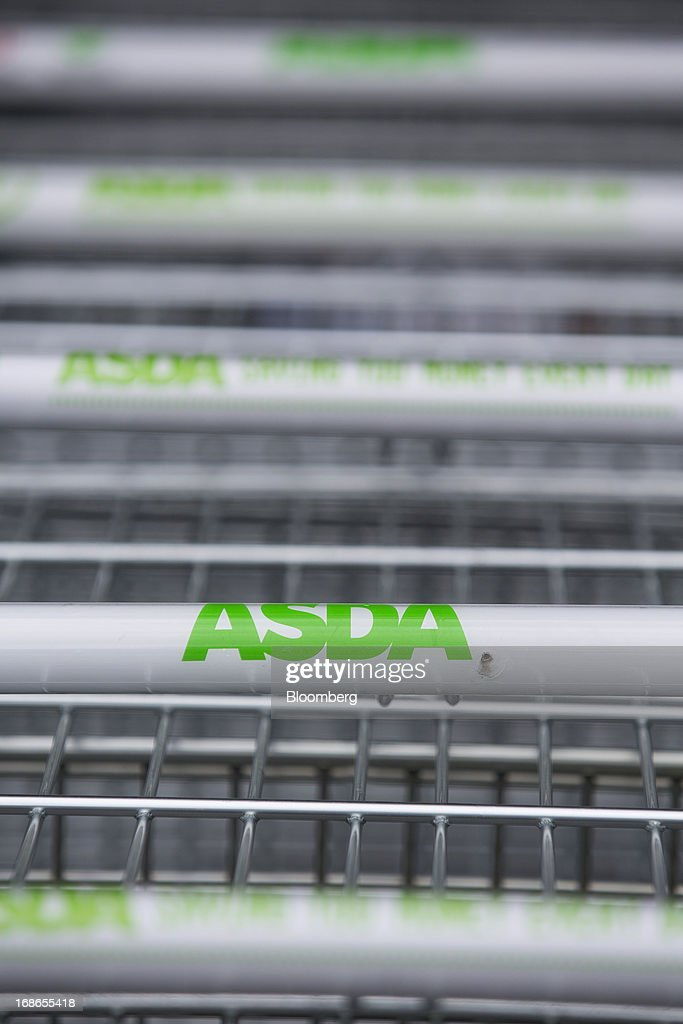 Logos sit on the handles of shopping carts outside an Asda supermarket store, operated by Wal-Mart Stores Inc., in the Wandsworth borough of London, U.K., on Monday, May 13, 2013. Asda, the U.K. supermarket chain owned by Wal-Mart Stores Inc., said sales rose 4.5 percent last year and it's investing 700 million pounds ($1 billion) into stores and online operations. Photographer: Jason Alden/Bloomberg via Getty Images