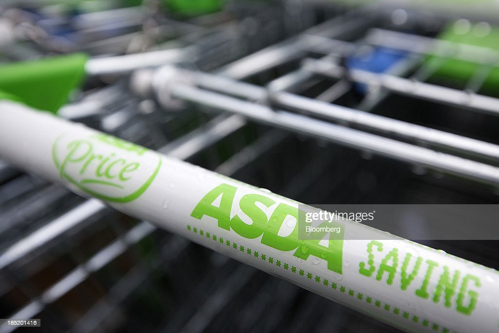 Logos sit on the handles of shopping carts outside an Asda supermarket, the U.K. retail arm of Wal-Mart Stores Inc., in Watford, U.K., on Thursday, Oct. 17, 2013. U.K. retail sales rose more than economists forecast in September as an increase in furniture demand led a rebound from a slump the previous month. Photographer: Simon Dawson/Bloomberg via Getty Images