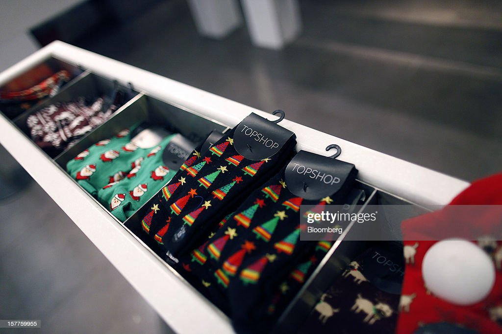 Logos sit on the tags of seasonal Christmas socks displayed for sale inside a Topshop store, owned by Arcadia Group Ltd., on Oxford Street in London, U.K., on Thursday, Dec. 6, 2012. Philip Green, the billionaire owner of the Arcadia fashion business, sold a 25 percent stake in the Topshop and Topman retail chains to Leonard Green & Partners LP, the co-owner of the J Crew fashion brand, in a deal valuing the businesses at 2 billion pounds ($3.2 billion). Photographer: Simon Dawson/Bloomberg via Getty Images
