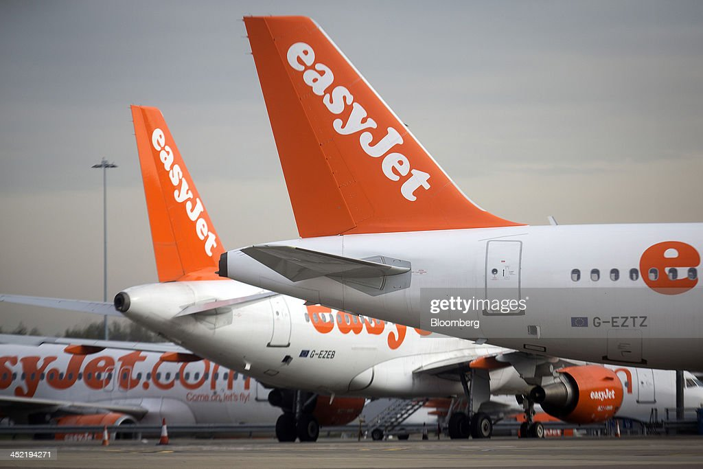 Logos sit on the tailfins of Airbus A319, left, and A320, right, aircraft operated by EasyJet Plc, as they sit parked on the tarmac at the airline's hub at London Luton Airport in Luton, U.K., on Tuesday, Nov. 26, 2013. Shares in International Consolidated Airlines Group SA (IAG) and EasyJet Plc climbed at least 2 percent, pushing a gauge of travel and leisure companies higher, as oil prices slid in reaction to Iran's nuclear deal with world powers. Photographer: Simon Dawson/Bloomberg via Getty Images